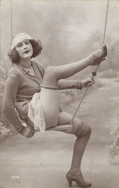 1920s Rolled stockings could be above or below the knee. This naughty postcard girl shows off her thigh rolled stockings at VintageDancer