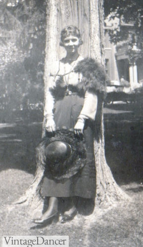 Very early 20s teen with along skirt and blouse, hat and short hairstyle