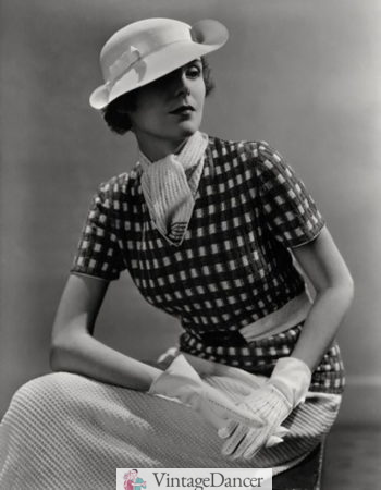 1930s fashion for women: A V neck knit top with a knit scarf tucked under
