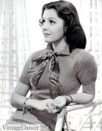 1940s jewelry: A charm bracelet is worn on her arm