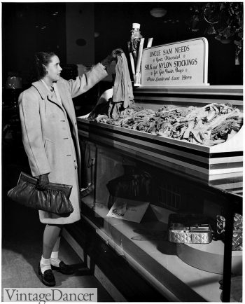 1942, a woman donates her silk stockings to be made into parachutes. She wears socks instead.