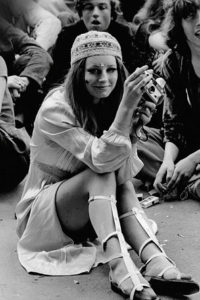Hippie woman in a white dress with bishop sleeves and a small hat