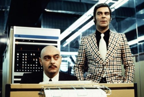 1973's German film 'World on a Wire' featuring two traditional office men in previously unheard of hairstyles - a thickly mustachioed but unimportant man and a boss with long sideburns and helmet-like hair at VintageDancer