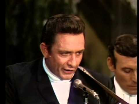60s mens hairstyles Johnny Cash in 1968 with turtleneck, blazer, and pompadour with sideburns at VintageDancer