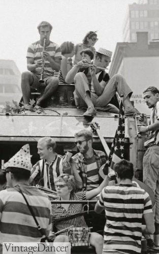 "The Merry Pranksters ""tootling"" with various instruments aboard Furthur in 1964. Many are wearing stripes or basic clothing, with the occasional odd accessory such as a birthday hat or a large American flag."