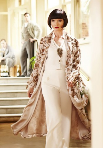 Miss Fisher wearing a white pant ensemble with kimono coat