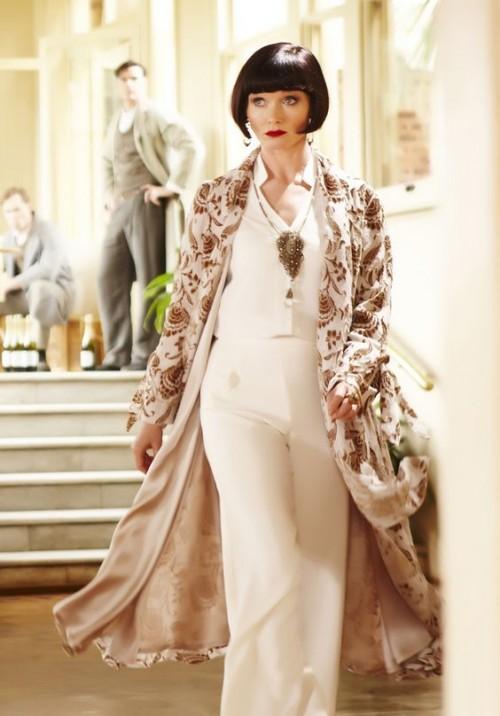 Miss Fisher wearing a white pant ensemble with kimono coat